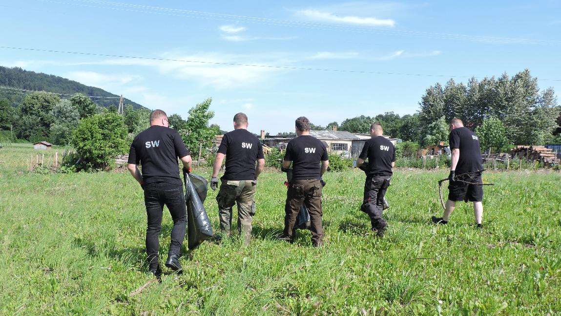 Funkcjonariusze Służby Więziennej sprzątają łąkę po powodzi.